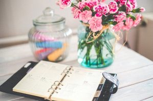 a planner on a desk with flowers